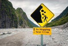 Sign warning hikers of dangerous falling rocks in a valley Stock Photo