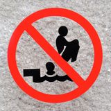 Sign forbidding dangerous jumping into a swimming pool. A sign warning people not jump into the pool in a tuck position as this could be dangerous. The symbol is stock photos