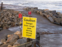 Sign warning of rough seas on East Pier. In Whitby, North Yorkshire, Royalty Free Stock Image