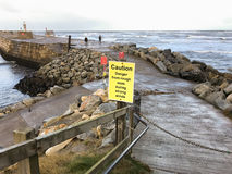 Sign warning of rough seas on East Pier. In Whitby, North Yorkshire, Stock Image