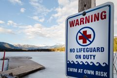 Sign warning that there is no lifeguard on duty at near a frozen winter lake. royalty free stock image