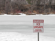 Unsafe ice sign on frozen lake Stock Image