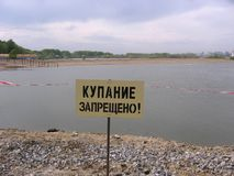 The sign warns swimming is forbidden on the beach you can not go into the water stock photos