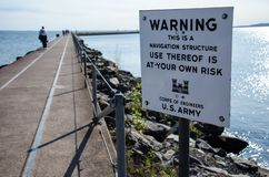 Sign warns tourists to be cautious when walking on the breakwater to the Two Harbors Breakwater Lighthouse. Use at your own risk royalty free stock image