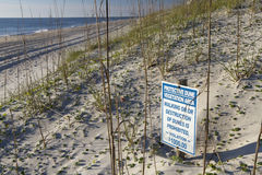 Sign Warns of Vegetation Destruction on Dunes by the Sea Stock Photos