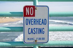 Sign warns visitors and fishermen of the no overhead casting rule on the pier. Taken in Manhattan Beach California.  royalty free stock photos
