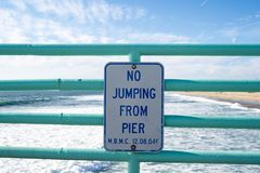 Sign warns visitors no jumping from the pier. Taken in Manhattan Beach, California.  royalty free stock image