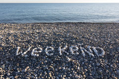 The sign Weekend made from white pebbles. On pebble beach on the sea Stock Photography