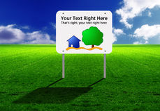 Sign on a wide green lawn. A sign with a house and tree and room for text in the middle of a wide green lawn and blue sky Royalty Free Stock Photography