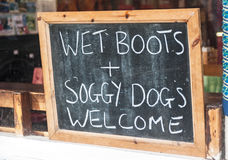 Sign in window to attract more customers. A sign to attract customers to a cafe or restaurant by inviting people with soggy wet dogs and wearing boots to dine stock photo