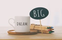 Sign With Text: DREAM BIG Next To Cup Of Coffee Over Wooden Table. Stock Images