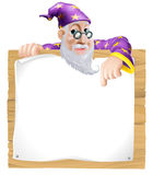 Sign Wizard. Friendly wizard man with a beard peeking over and pointing at a wooden sign Royalty Free Stock Photo