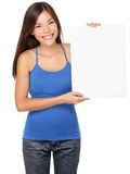 Sign woman holding showing white sign. Sign woman holding showing white blank paper placard. Smiling happy young asian girl in tank top isolated on white Stock Photography