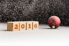 2016 sign on wooden cubes and red christmas ball lying on a snow Royalty Free Stock Images