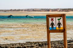 Sign in a Wooden Frame on the Beach Near the Egyptian Red Sea Prohibiting Walking on Corals with Two Boats in the Backround royalty free stock photos