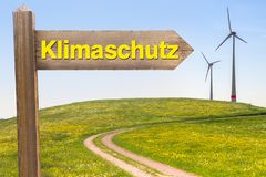 Climate Protection Concept in German. Sign with the Word Climate Protection in German and Wind Turbines in the Background royalty free stock images