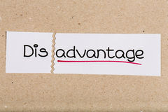 Sign with word disadvantage turned into advantage. Two pieces of white paper with the word disadvantage turned into advantage Royalty Free Stock Photos