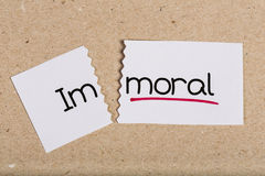 Sign with word immoral turned into moral. Two pieces of white paper with the word immoral turned into moral Stock Photos