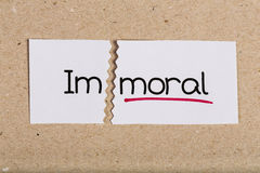 Sign with word immoral turned into moral. Two pieces of white paper with the word immoral turned into moral Royalty Free Stock Photos