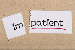 Sign with word impatient turned into patient. Two pieces of white paper with the word impatient turned into patient stock images