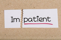 Sign with word impatient turned into patient. Two pieces of white paper with the word impatient turned into patient royalty free stock images