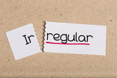 Sign with word irregular turned into regular. Two pieces of white paper with the word irregular turned into regular Royalty Free Stock Image