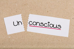 Sign with word unconscious turned into conscious. Two pieces of white paper with the word unconscious turned into conscious Stock Image