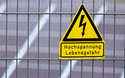 Sign with the words High voltage - Danger to life in German in front of solar panels Royalty Free Stock Image