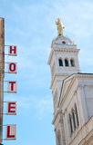Sign written hotels silhouetted against the sky Stock Photos