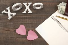 Sign XOXO,Two Hearts, Pen, Paper, Money On Wood Background Stock Photo