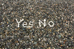 The sign Yes No made from white pebbles. On pebble beach on the sea Royalty Free Stock Photo