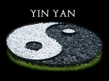 Sign of yin yang laid out of black and white stones isolated on black background. Ying Yang white text on black royalty free stock images