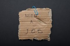 Sign `you need work` on torn cardboard, black background. royalty free stock photos