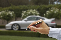 Sign your life away. Mans hand holding ball point pen,blue pinstriped shirt, soft focus sports car in the background Royalty Free Stock Images