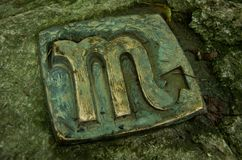 Sign of the Zodiac- Scorpio. Sign of Scorpio- sculpture from metal placed in stone. The `Sun path` in Å tramberk, Czech Republic royalty free stock photography