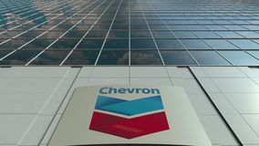 Signage board with Chevron Corporation logo. Modern office building facade time lapse. Editorial 3D rendering. Outdoor signage board with Chevron Corporation stock video footage