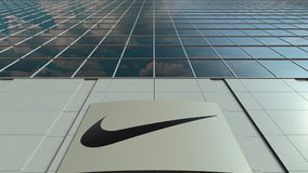 Signage board with Nike inscription and logo. Modern office building facade. Editorial 3D rendering