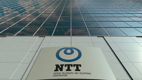 Signage board with Nippon Telegraph and Telephone Corporation NTT logo. Modern office building facade. Editorial 3D Stock Image
