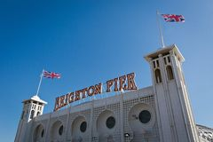 A signage of Brighton Pier with the English flag Stock Image