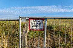 Signage of a construction site at a fence. Translation: German for `Enter the construction site prohibited! Parents are responsible for their children stock photos