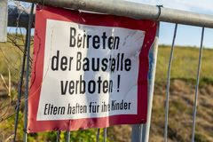 Signage of a construction site at a fence. Translation: German for `Enter the construction site prohibited! Parents are responsible for their children royalty free stock images