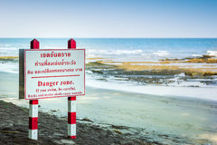 Signage danger beach. Danger oyster rock zone on the beach Stock Images