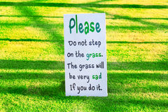 Signage on the grass. Message please do not step on the grass, the grass will be very sad if you do it signage on the grass Stock Image