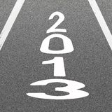 Signal Arrow and Word 2013 on Asphalt Road Background. The Signal White Arrow and Word 2013 Painted On A Road Surface Freshly Covered with Asphalt Concrete Stock Photo
