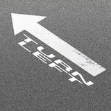 Signal Arrow and Word Turn Left on Asphalt Road Background Royalty Free Stock Photo