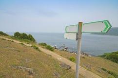 Signal de direction blanc avec la route en pierre Images stock