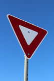 Signal de ralentissement contre le ciel bleu Images stock