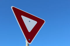 Signal de ralentissement contre le ciel bleu Photographie stock libre de droits