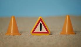 Signal der Aufmerksamkeit zusammen mit Kegeln der Arbeit über Sand der Unterseite des Strandes und des blauen Himmels und mit Räu lizenzfreie stockbilder