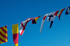 Signal flags. Maritime signal flags on a blue sky background Stock Image